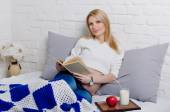 Pregnant woman lying on a sofa and reading a book — Stock Photo