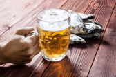 Hand with beer glass and dried fish. — Stock Photo