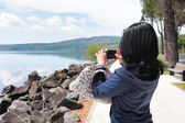 Woman Taking Photos Of Lake With Smartphone — Stock Photo