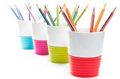 Colored pencil crayons in colorful containers — Stock Photo