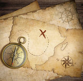 Aged brass nautical compass on table with old treasure maps — Stock Photo