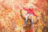 Happy parent and kid walking together outdoor in autumn park. — Foto de Stock
