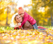Parent and kid lying together on falling leaves. Happy family ou — Stock Photo