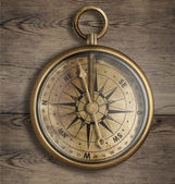 Old brass compass on wood table close up — Stock Photo