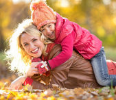 Parent and child lying together on falling leaves. Family outdoo — Foto de Stock