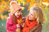 Happy parent and kid holding autumn yellow leaves outdoor. — Foto de Stock