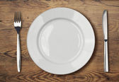 White empty dinner plate setting on wooden table — Stock Photo