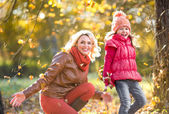 Happy parent and kid outdoor playing with autumn yellow leaves — Foto de Stock