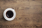 Black coffee cup on old wooden table top view — Stock Photo