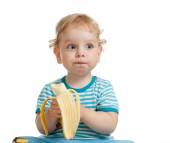 Kid boy eating banana isolated — ストック写真