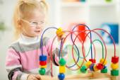 Kid in eyeglases playing colorful toy in home interior — Stock Photo