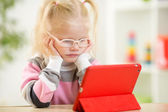 Happy child in glasses looking at mini tablet pc screen — Stock Photo