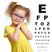 Smiling girl in glasses with eye chart isolated — ストック写真