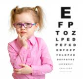 Serious girl in glasses with eye chart isolated — ストック写真