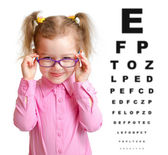 Smiling girl putting on glasses with blurry eye chart behind her — ストック写真