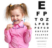 Smiling girl took off glasses with blurry eye chart behind her — Stock fotografie