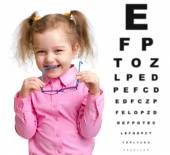 Smiling girl took off glasses with blurry eye chart behind her — ストック写真