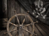 Pirates ship steering wheel with old jolly roger flag — Stock Photo
