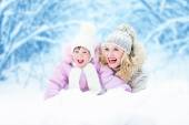 Happy parent mother and kid lying in snow outdoor — Stock Photo