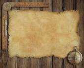 Old treasure map on wooden desk with compass and ruler — Stock Photo