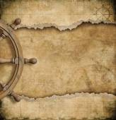 Steering wheel and torn vintage nautical map — Stock Photo