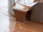 Hot milk chocolate flow or stream on factory — Stock Photo