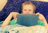 Boy lies in bed and plays — Stock Photo