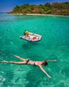 Woman swimming near boat in sea — Stock Photo