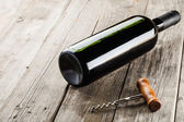 Bottle of wine and corkscrew on wooden backgroumd — Stockfoto