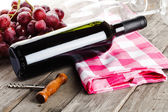 Bottle of wine corkscrew amd grapes on wooden table — Stok fotoğraf