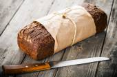 Fresh bread wrapped in paper — Stock Photo