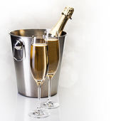 Champagne bottle in bucket with glasses of champagne — Stock Photo