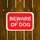 Beware of a dog sign on a wooden fence — Stock Vector