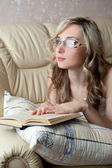 Sexy woman with glasses reading book — Stockfoto