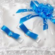 White pillow for wedding rings with blue ribbons — Stock Photo #54228323