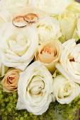 Gold wedding rings on a bouquet of flowers for the bride  — Foto de Stock