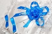 White pillow for wedding rings with blue ribbons — Stock Photo