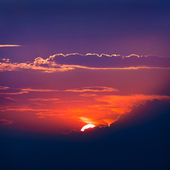 Verlicht door de zon wolken bij zonsondergang op een achtergrond van blauw — Stockfoto