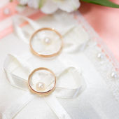 Wedding gold rings bride and groom on decorative pillow. — Stockfoto