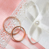 Wedding gold rings bride and groom on decorative pillow. — Stock Photo