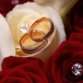 Gold wedding rings on a bouquet of flowers for the bride  — Stock Photo