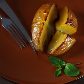 Potatoes baked on a clay plate on the dining table. — Stock fotografie