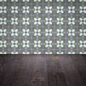 Wood table top and blur vintage ceramic tile pattern wall — Stock fotografie