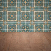 Wood table top and blur vintage ceramic tile pattern wall — Stock Photo