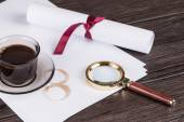 Coffee cup, paper sheets and detective magnifying glass — Stock Photo