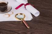 Wrapped paper sheets and magnifying glass — Stock Photo