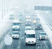 Snowy winter road with cars driving on roadway in snow storm — Stock Photo
