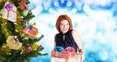 Beautiful Women and eve tree with holidays Gifts over snow blue abstract Christmas background — Stock Photo