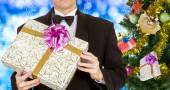 Men in tuxedo and Christmas eve tree with Gifts — Stockfoto
