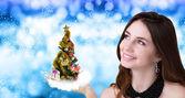 Beautiful Caucasian Women with green  Christmas eve tree over hand — Stock Photo